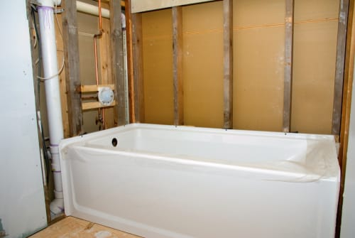 A bathtub that is being installed by a plumber during a washroom renovation.